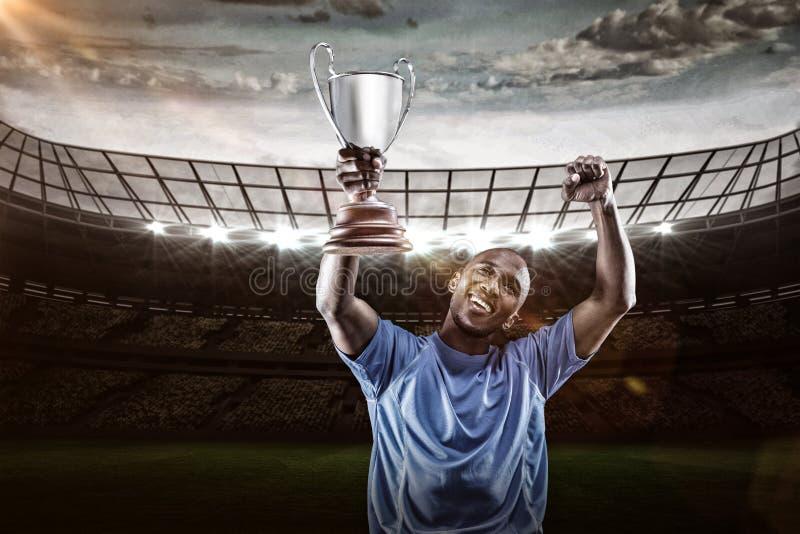 Σύνθετη εικόνα τρισδιάστατη του ευτυχούς κοιτάγματος αθλητικών τύπων επάνω και ενθαρρυντικού κρατώντας το τρόπαιο στοκ φωτογραφία με δικαίωμα ελεύθερης χρήσης