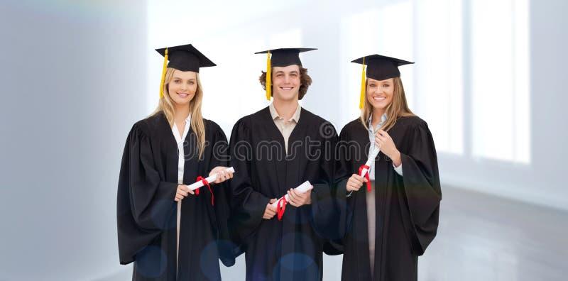 Σύνθετη εικόνα τριών σπουδαστών στη διαβαθμισμένη τήβεννο που κρατούν ένα δίπλωμα στοκ φωτογραφίες με δικαίωμα ελεύθερης χρήσης