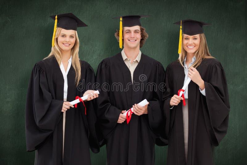 Σύνθετη εικόνα τριών σπουδαστών στη διαβαθμισμένη τήβεννο που κρατούν ένα δίπλωμα στοκ φωτογραφία