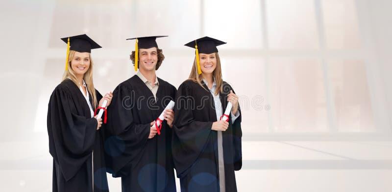 Σύνθετη εικόνα τριών χαμογελώντας σπουδαστών στη διαβαθμισμένη τήβεννο που κρατούν ένα δίπλωμα στοκ εικόνα