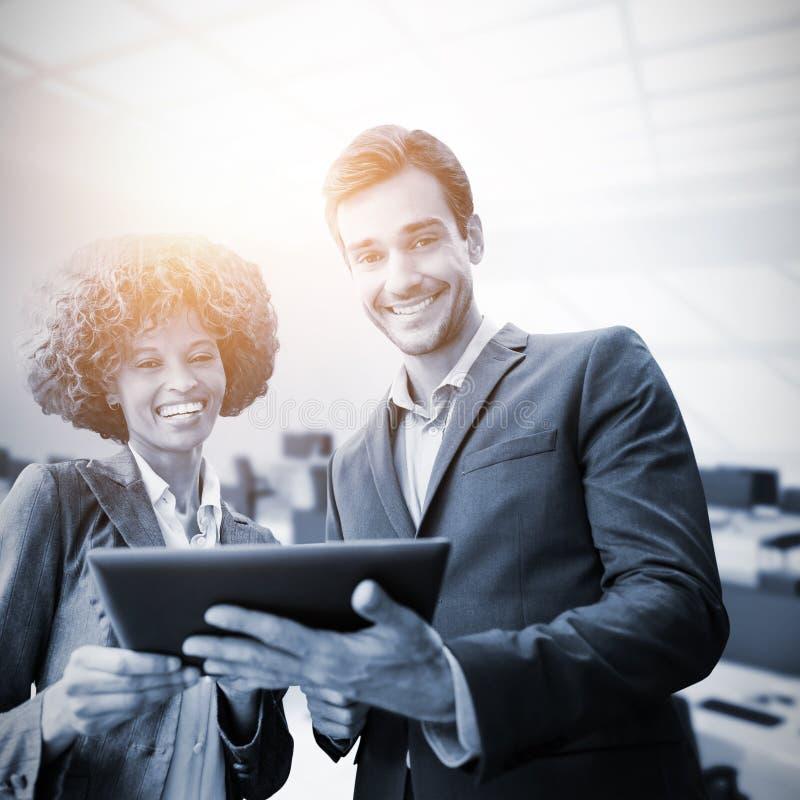 Σύνθετη εικόνα των επιχειρηματιών που στέκονται με μια ταμπλέτα στοκ εικόνες