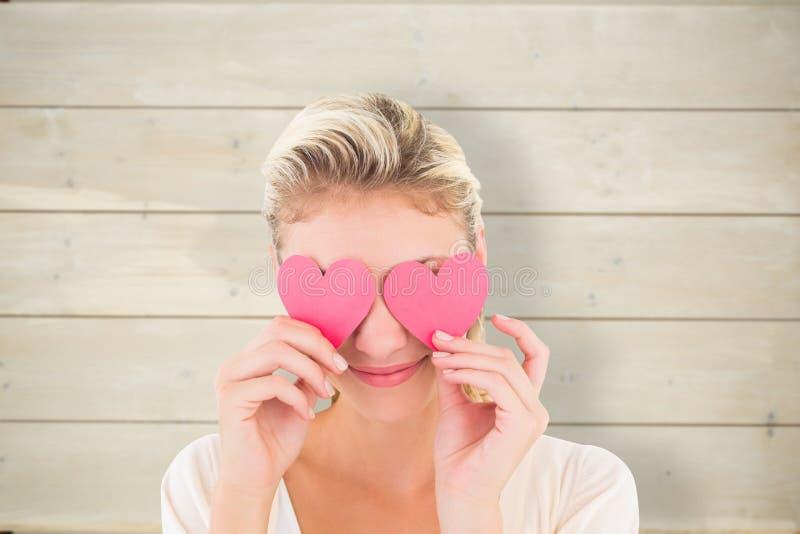 Σύνθετη εικόνα των ελκυστικών νέων ξανθών καρδιών εκμετάλλευσης πέρα από τα μάτια στοκ φωτογραφία