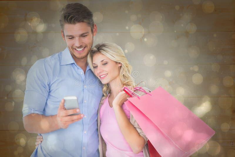 Σύνθετη εικόνα των ελκυστικών νέων τσαντών αγορών εκμετάλλευσης ζευγών που εξετάζουν το smartphone στοκ εικόνα