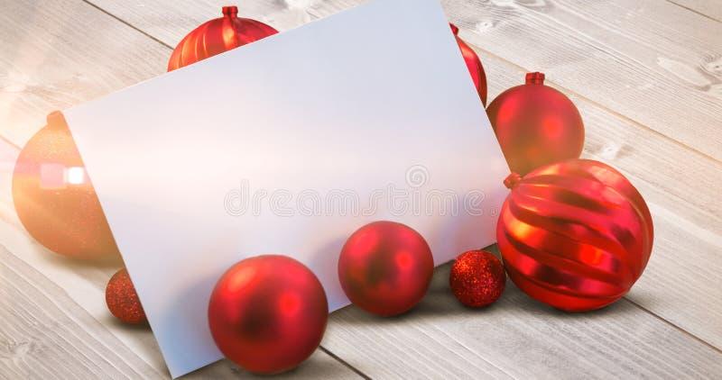 Σύνθετη εικόνα των κόκκινων μπιχλιμπιδιών Χριστουγέννων που περιβάλλουν την άσπρη σελίδα στοκ φωτογραφίες
