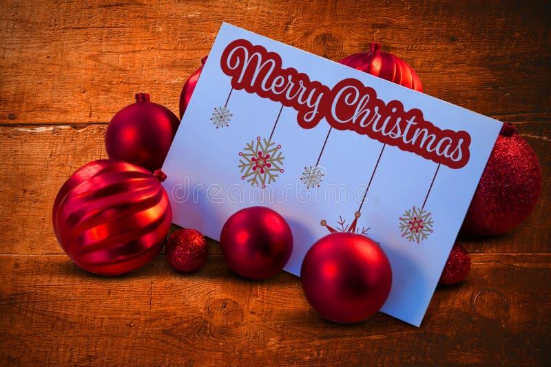 Σύνθετη εικόνα των κόκκινων μπιχλιμπιδιών Χριστουγέννων που περιβάλλουν την άσπρη σελίδα διανυσματική απεικόνιση