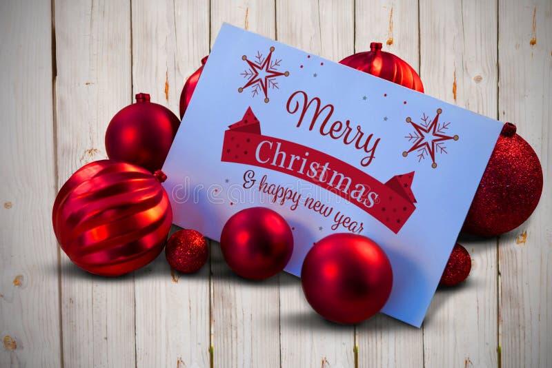 Σύνθετη εικόνα των κόκκινων μπιχλιμπιδιών Χριστουγέννων που περιβάλλουν την άσπρη σελίδα απεικόνιση αποθεμάτων