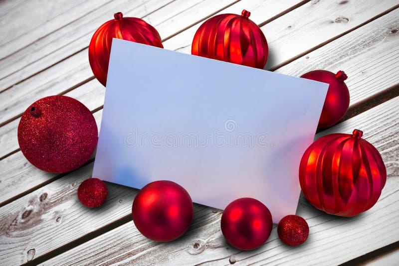 Σύνθετη εικόνα των κόκκινων μπιχλιμπιδιών Χριστουγέννων που περιβάλλουν την άσπρη σελίδα στοκ φωτογραφία με δικαίωμα ελεύθερης χρήσης