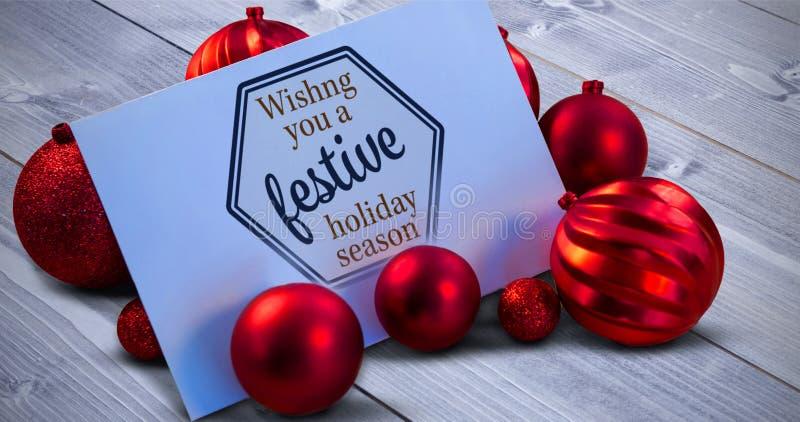 Σύνθετη εικόνα των κόκκινων μπιχλιμπιδιών Χριστουγέννων που περιβάλλουν την άσπρη σελίδα στοκ εικόνα