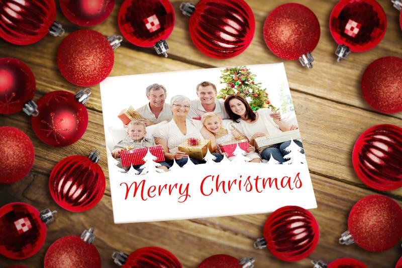 Σύνθετη εικόνα των μπιχλιμπιδιών Χριστουγέννων στον πίνακα στοκ φωτογραφίες