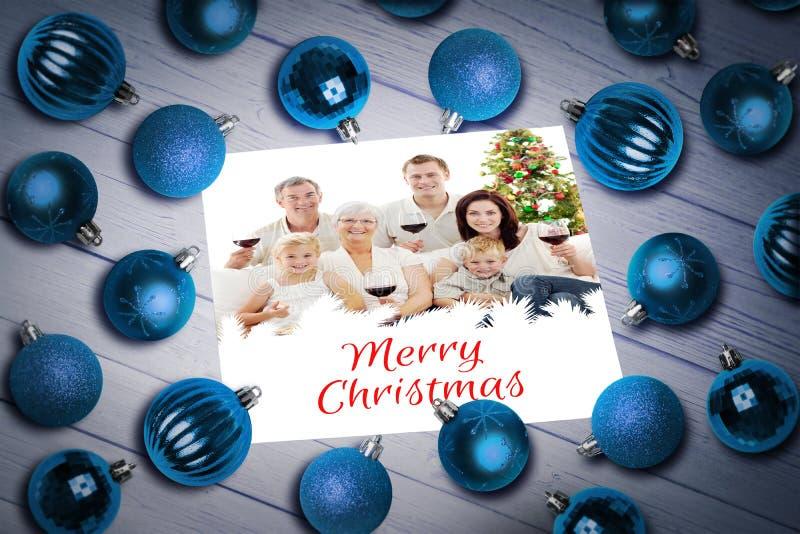 Σύνθετη εικόνα των μπιχλιμπιδιών Χριστουγέννων στον πίνακα στοκ εικόνα