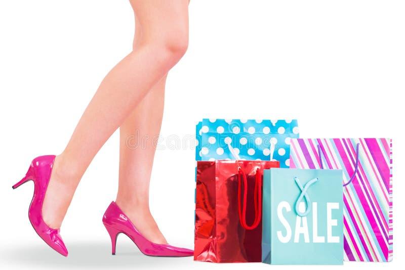 Σύνθετη εικόνα των ποδιών της γυναίκας στα υψηλά τακούνια με τις τσάντες αγορών στοκ εικόνα με δικαίωμα ελεύθερης χρήσης