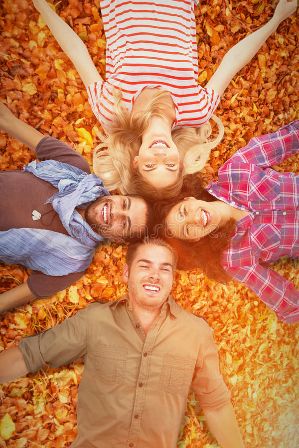 Σύνθετη εικόνα των φίλων που βρίσκονται σε έναν κύκλο και που χαμογελούν στη κάμερα στοκ εικόνες με δικαίωμα ελεύθερης χρήσης