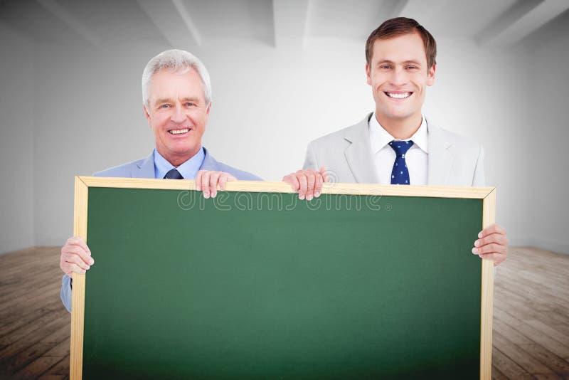Σύνθετη εικόνα των χαμογελώντας εμπόρων που κρατούν το κενό σημάδι στοκ φωτογραφίες