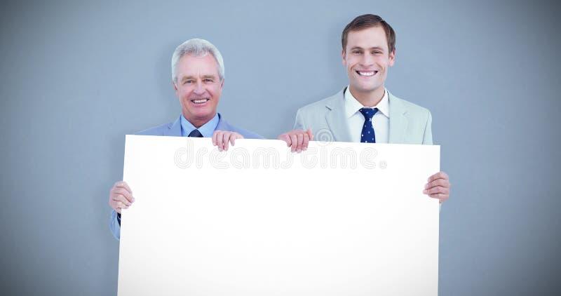 Σύνθετη εικόνα των χαμογελώντας εμπόρων που κρατούν το κενό σημάδι στοκ εικόνες με δικαίωμα ελεύθερης χρήσης