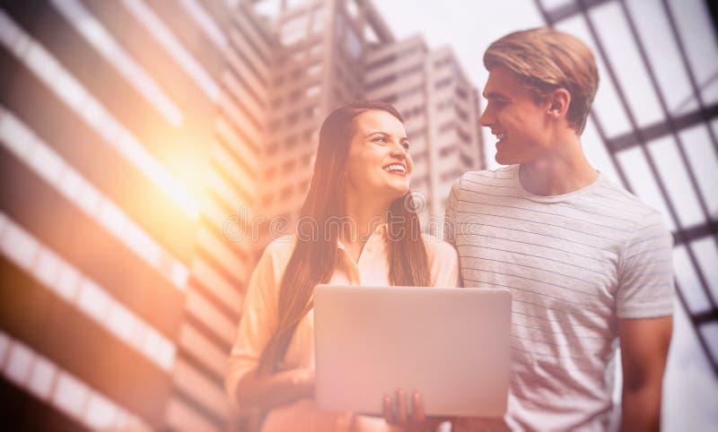 Σύνθετη εικόνα των χαμογελώντας συναδέλφων που εξετάζουν ο ένας τον άλλον χρησιμοποιώντας το lap-top στοκ φωτογραφία με δικαίωμα ελεύθερης χρήσης