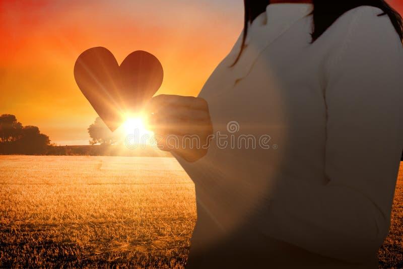 Σύνθετη εικόνα midsection του εγγράφου μορφής καρδιών εκμετάλλευσης γυναικών στοκ φωτογραφία με δικαίωμα ελεύθερης χρήσης