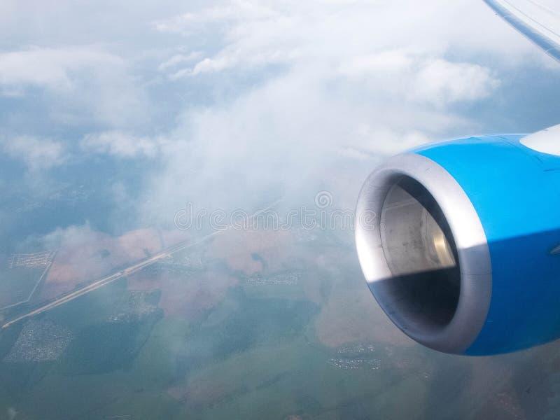 Σύννεφα, δρόμοι και τομείς, μηχανή και φτερό του αεροπλάνου Εναέρια άποψη από το φωτιστικό αεροπλάνων στοκ φωτογραφία με δικαίωμα ελεύθερης χρήσης