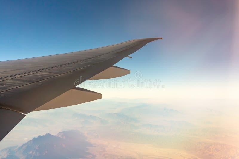 Σύννεφα κάτω από το φτερό ενός αεροπλάνου Καταπληκτική άποψη από το παράθυρο του αεροπλάνου κατά τη διάρκεια της πτήσης στοκ εικόνες