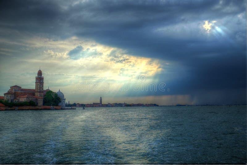 Σύννεφα και ήλιος πέρα από τη λιμνοθάλασσα Άποψη του νησιού του SAN Giorgio στοκ εικόνα