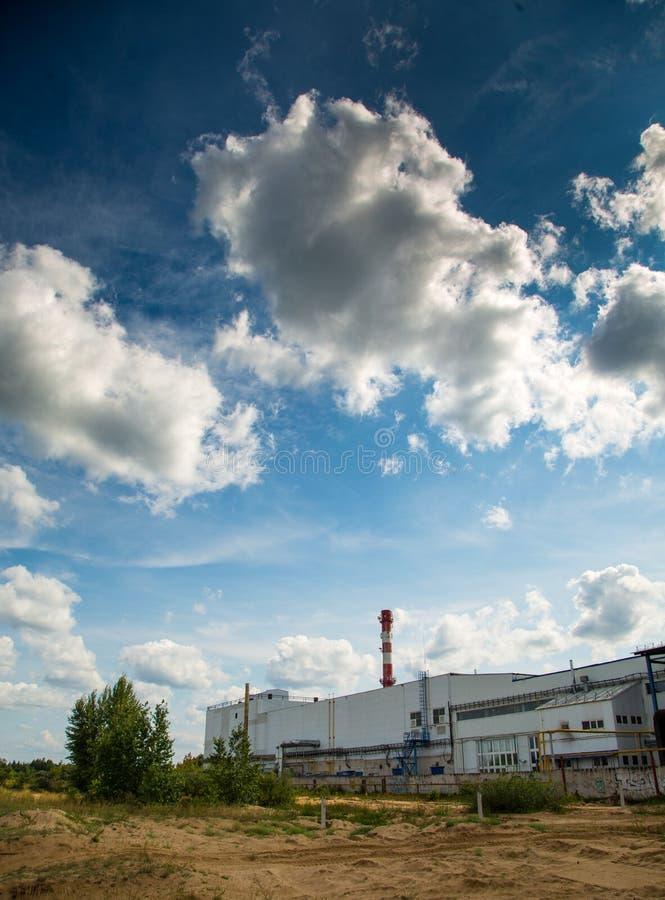 Σύννεφα στο μπλε ουρανό πέρα από τις εγκαταστάσεις Οικολογία, περιβάλλον στοκ εικόνες
