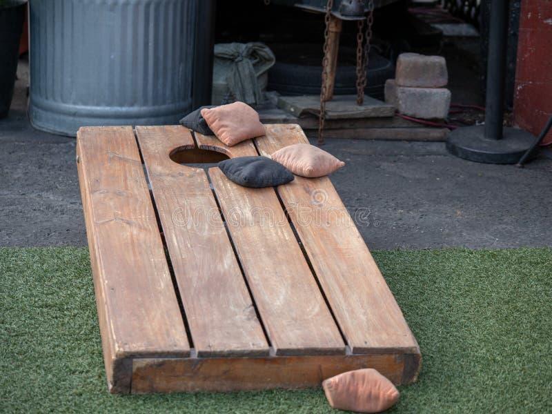 Σύνολα beanbags στο ανταγωνιστικό παιχνίδι του cornhole σε μια πλατφόρμα ξυλείας στοκ φωτογραφία