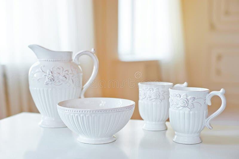 Σύνολο άσπρων κεραμικών εργαλείων κουζινών, πιάτα στον άσπρο πίνακα στο μεγάλο φωτεινό δωμάτιο μπροστά από το παράθυρο στοκ φωτογραφία με δικαίωμα ελεύθερης χρήσης