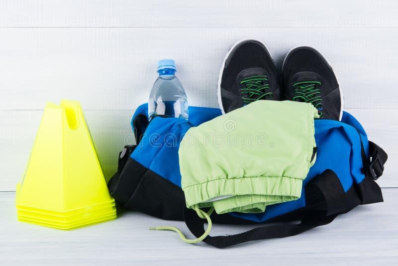 Σύνολο αθλητικών πραγμάτων για τον αθλητισμό παιχνιδιού, τα τρέχοντας παπούτσια και μια μορφή σε μια τσάντα και ένα μπουκάλι νερό στοκ φωτογραφία με δικαίωμα ελεύθερης χρήσης