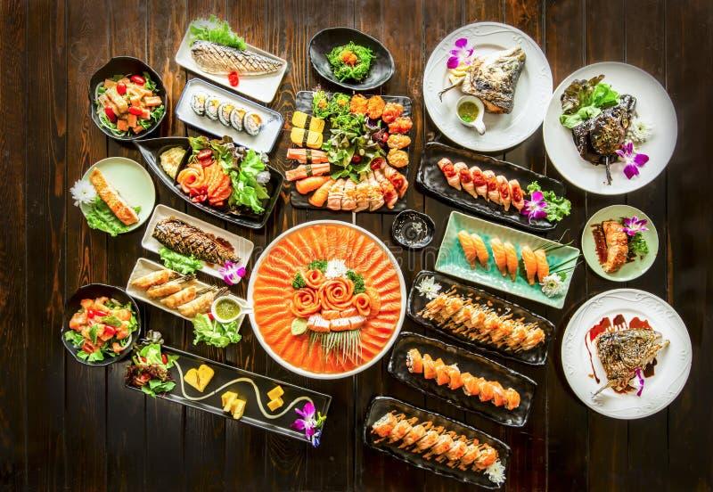 Σύνολο από σούσι και ρολά σολομού, ψαροκέφαλο ψάρι με μαύρο ρουστικό ξύ στοκ εικόνες