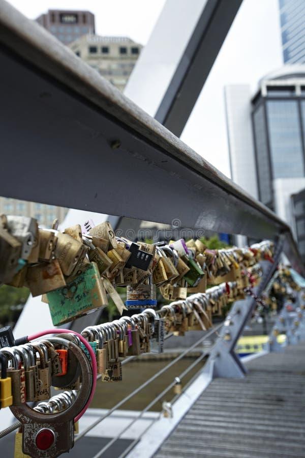 Σύνολο γεφυρών των ζωηρόχρωμων κλειδαριών αγάπης με μερικά ονόματα που γράφονται σε το στοκ εικόνα