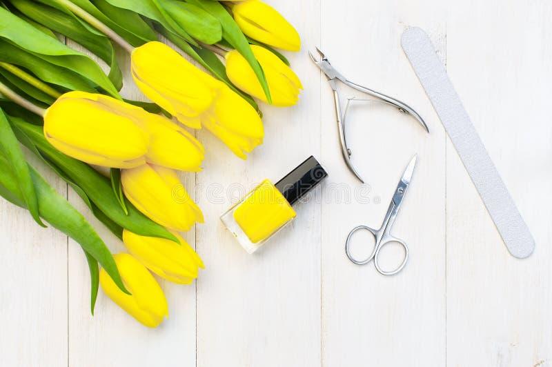 Σύνολο για το μανικιούρ ή το pedicure, φωτεινή στιλβωτική ουσία καρφιών, ψαλίδι, nippers, λαβίδες και nailfile με τις κίτρινες το στοκ εικόνα