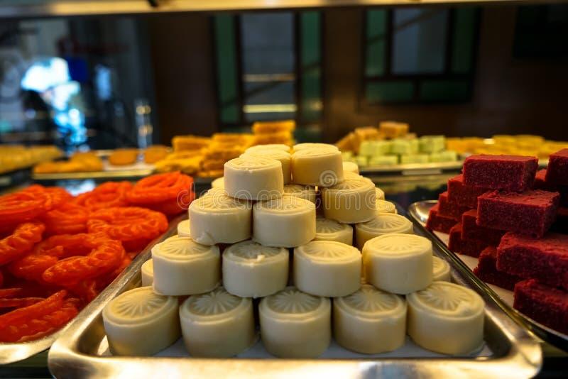 Σύνολο δίσκων του γλυκού άσπρου, κόκκινου, πορτοκαλιού και κίτρινου ινδικού κέικ επιδορπίων σωρών στην προθήκη αρτοποιείων στοκ εικόνες