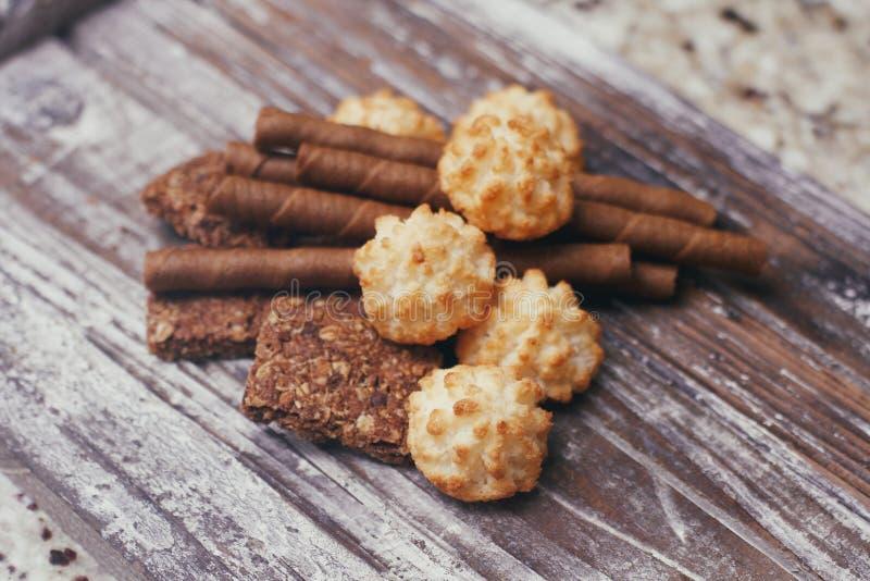 Σύνολο διαφορετικών γλυκών βιομηχανιών ζαχαρωδών προϊόντων στον ξύλινο πίνακα Σοκολάτα, βάφλες, μπισκότα καρύδων, μπισκότα στοκ εικόνες