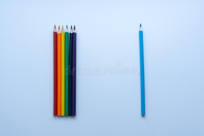 Σύνολο επτά αιχμηρών τόξο-χρωματισμένων μολυβιών με το χωρισμένο μπλε μολύβι, από τη τοπ άποψη σχετικά με ένα άσπρο υπόβαθρο στοκ εικόνες