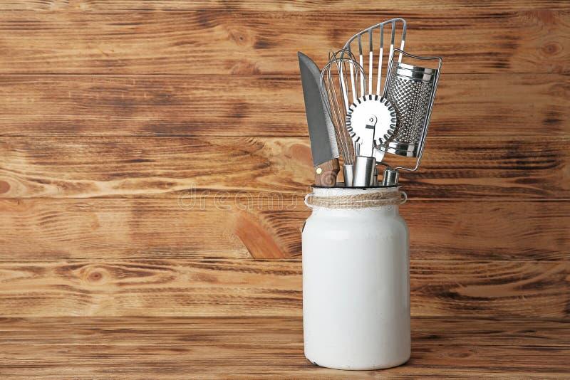 Σύνολο εργαλείων κουζινών στο καρδάρι γάλακτος στον πίνακα στοκ φωτογραφία