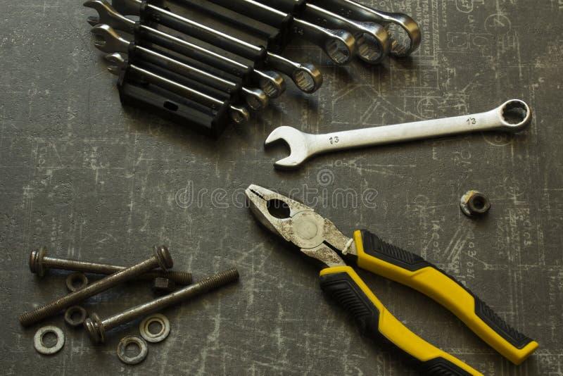 Σύνολο εργαλείων πενσών, γαλλικών κλειδιών, μπουλονιών και καρυδιών στην αφηρημένη γκρίζα επιφάνεια στοκ εικόνα