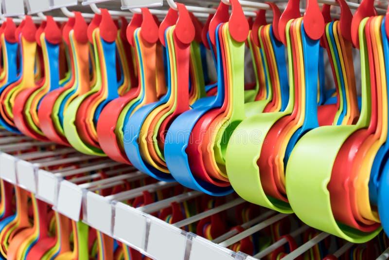 Σύνολο ζωηρόχρωμων πλαστικών μετρώντας κουταλιών που κρεμούν στο ράφι στοκ φωτογραφίες