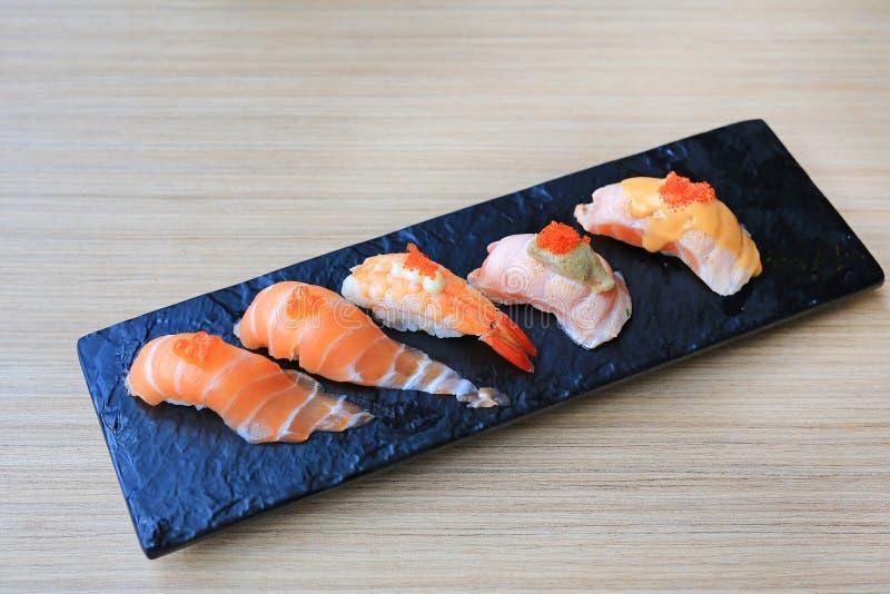 Σύνολο θαλασσινών σουσιών που εξυπηρετείται στο μαύρο πιάτο πετρών στον ξύλινο πίνακα Ιαπωνική κουζίνα στοκ εικόνες