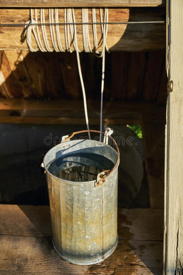 Σύνολο κάδων μετάλλων του γλυκού νερού που λαμβάνεται ακριβώς από παλαιό έναν ξύλινο σύρω-καλά στην επαρχία σε μια θερινή ημέρα στοκ εικόνα