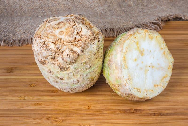 Σύνολο και οι μισές από τις ρίζες σέλινου σε μια ξύλινη επιφάνεια στοκ εικόνα με δικαίωμα ελεύθερης χρήσης