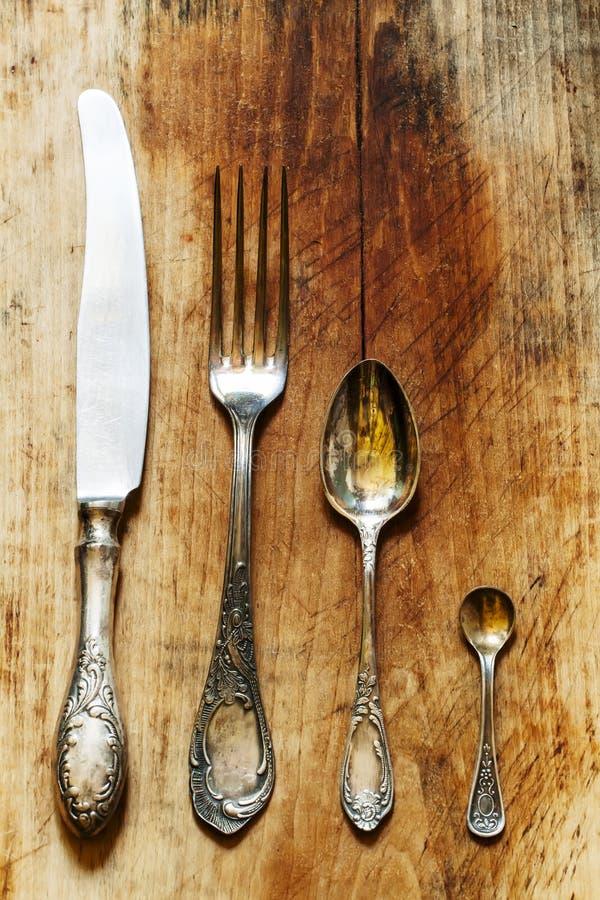 Σύνολο μαχαιροπήρουνων: κουτάλι, δίκρανο, μαχαίρι στο εκλεκτής ποιότητας ύφος στο παλαιό woode στοκ εικόνα