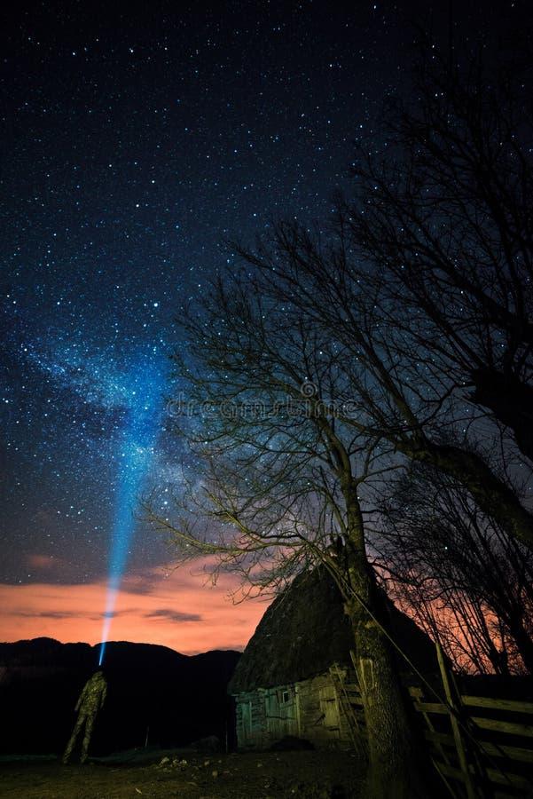 Σύνολο νυχτερινού ουρανού των αστεριών με μερικά σύννεφα και το γαλακτώδη γαλαξία τρόπων και ενός ατόμου στο πρώτο πλάνο με έναν  στοκ φωτογραφίες