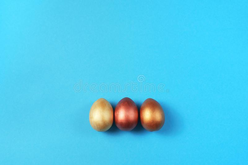 Σύνολο Πάσχας χρυσών αυγών στις φωτεινές μπλε διακοσμήσεις διακοπών Πάσχας υποβάθρου στοκ φωτογραφίες
