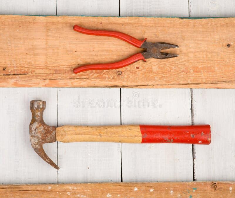 Σύνολο παλαιών εργαλείων - σφυρί, πένσες στο ξύλινο υπόβαθρο στοκ εικόνες