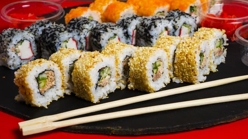 Σύνολο παραδοσιακών ιαπωνικών τροφίμων σε ένα σκοτεινό υπόβαθρο Το σούσι κυλά, nigiri, ακατέργαστη μπριζόλα σολομών, ρύζι, τυρί κ στοκ φωτογραφίες