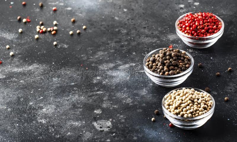 Σύνολο πιπεριών Μαύρος, άσπρος και ρόδινος αυξήθηκε πιπέρια στα κύπελλα, ανάμεικτα καρυκεύματα στον γκρίζο πίνακα κουζινών, εκλεκ στοκ φωτογραφίες με δικαίωμα ελεύθερης χρήσης