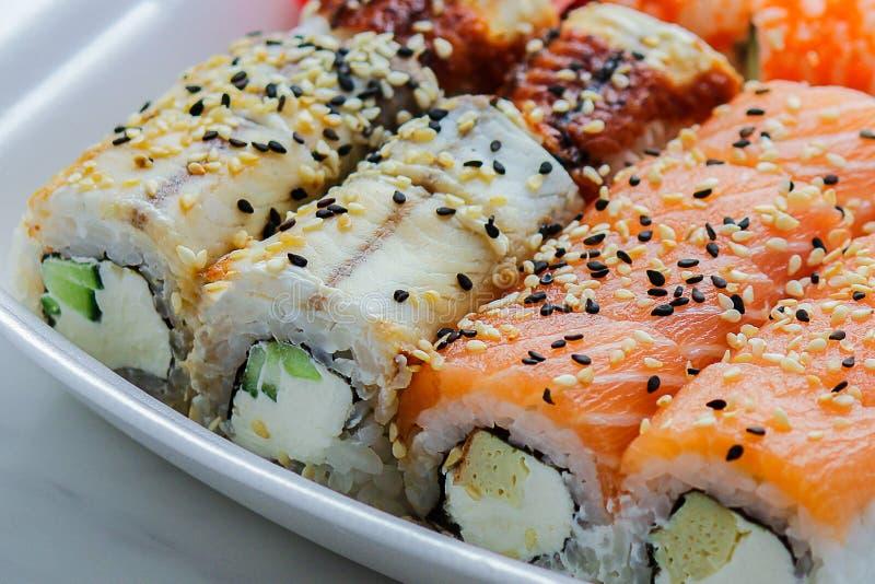 Σύνολο ρόλων σουσιών και sashimi Φρέσκα σούσια με το σολομό, τις γαρίδες, το χέλι, το wasabi και την πιπερόριζα στοκ φωτογραφίες