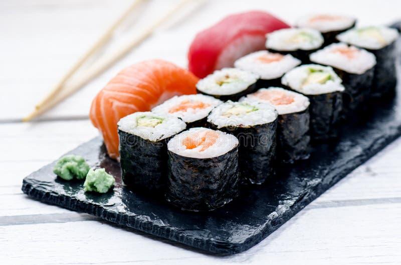 Σύνολο σουσιών που εξυπηρετείται σε μια μαύρη πλάκα Ρόλοι και sashimi σουσιών σε έναν ξύλινο άσπρο πίνακα Θαλασσινά ψάρια ακατέργ στοκ φωτογραφία