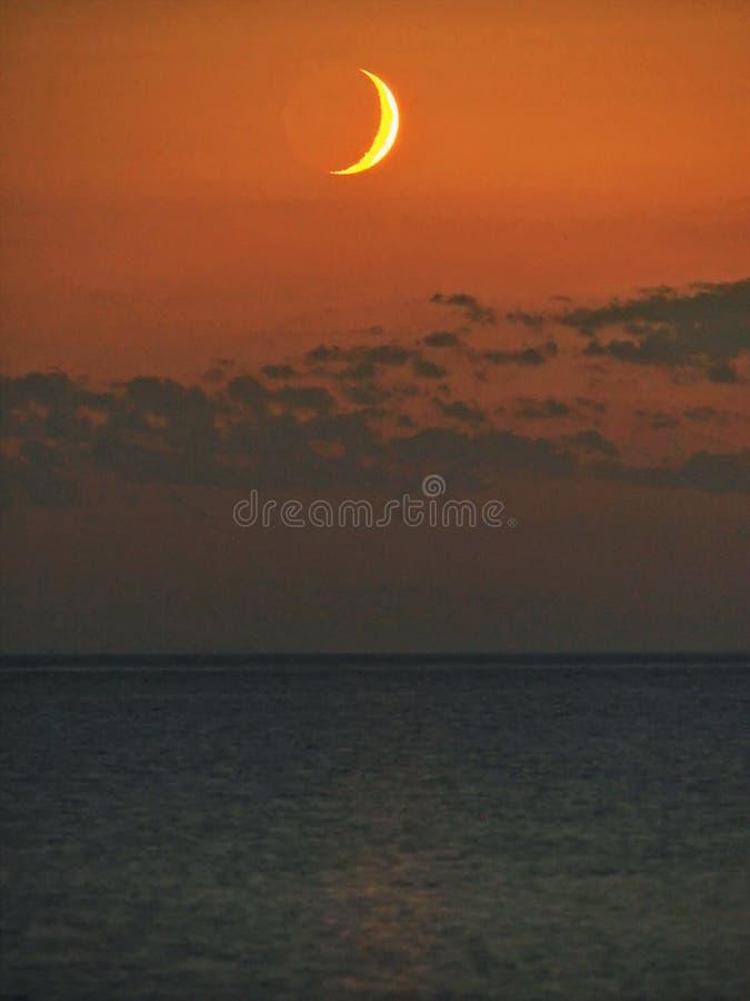 Σύνολο φεγγαριών και πορτοκαλής ουρανός μετά από το ηλιοβασίλεμα στοκ φωτογραφία