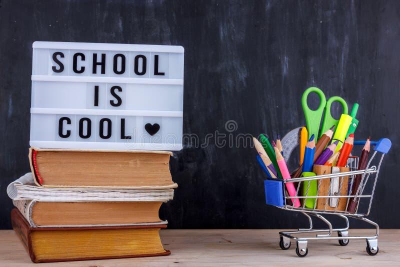 Σύνολο χρωματισμένων μολυβιών και δεικτών για το σχολείο σε ένα κάρρο αγορών Το γράφοντας σχολείο έχει δροσιά σε έναν σωρό των βι στοκ εικόνες