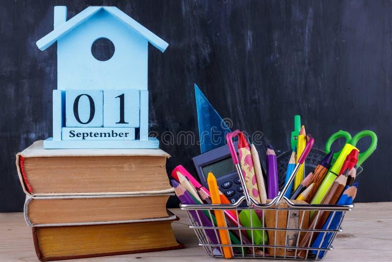 Σύνολο χρωματισμένων μολυβιών και δεικτών για το σχολείο σε ένα κάρρο αγορών 1 του ημερολογίου Σεπτεμβρίου σε έναν σωρό των βιβλί στοκ εικόνες